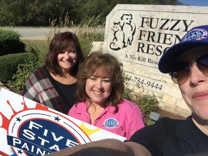 Five Star Painting Crew Take Selfie in Front of Cleaned and Re-painted Fuzzy Friends Rescue Sign